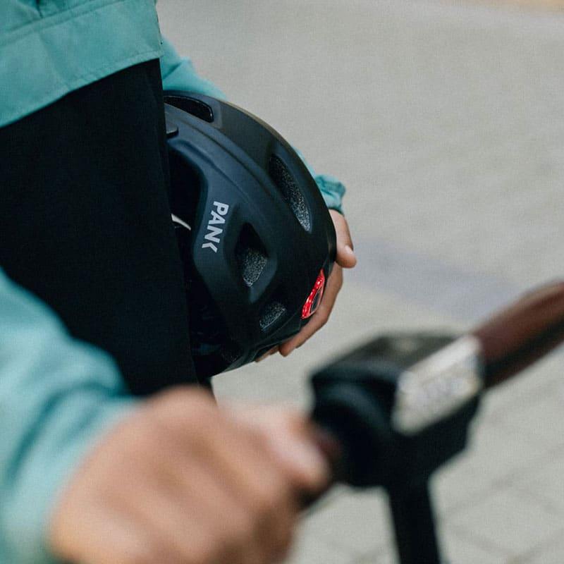 chico cargando casco patinete eléctrico